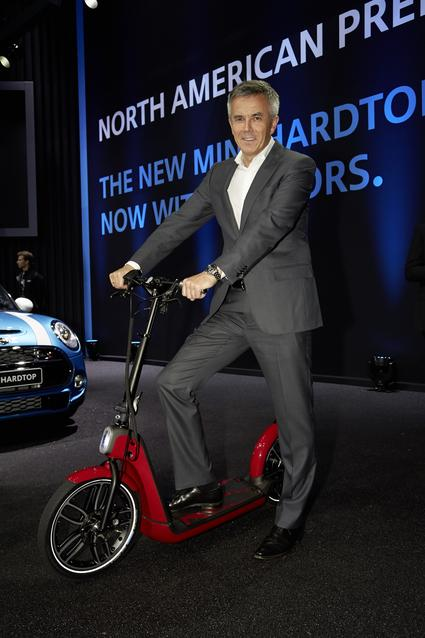 Peter Schwarzenbauer, Member of the Board of Management of BMW AG, stands with the MINI Citysurfer.